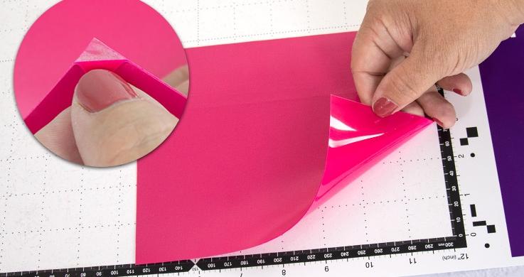 Legen Sie Ihre Aufbügelfolie mit der transparenten Plastikseite nach unten in den Schneideplotter ein. Lösen Sie Ihre Folie an der Ecke etwas ab um die richtige Seite zu finden.