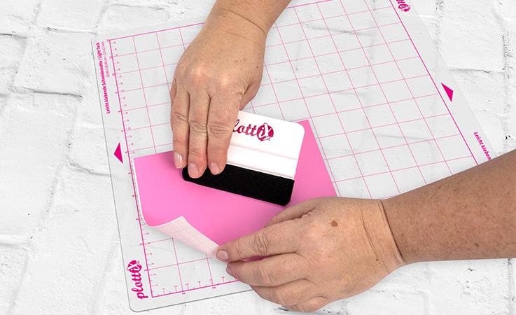 Legen Sie Ihre Vinylfolie mit der Trägerfolie nach unten auf Ihre Schneidematte.